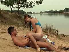 A young couple is fucking in the sand at a lake shore. The girl is...